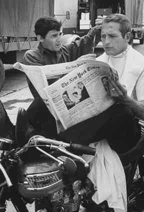 Paul Newman sits atop a motorcycle reading a newspaper while he receives a spontaneous trim from Barber Jay Sebring on the set of Harper, 1965.
