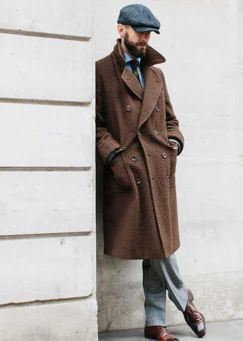 Simon Crompton represents excellent taste in both British style and Italian tailoring, with a peaked cap and Casentino Ulster Coat by Rubinacci. Photo by Jamie Ferguson.