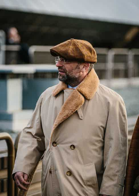A gentleman in Florence wears a brown peaked cap with a large gold overcheck and tonal shearling coat. Photo by Jamie Ferguson.