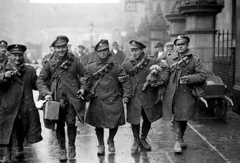 A group of British soldiers all wearing functional double-breasted overcoats, which later would become a wardrobe staple, circa 1917.