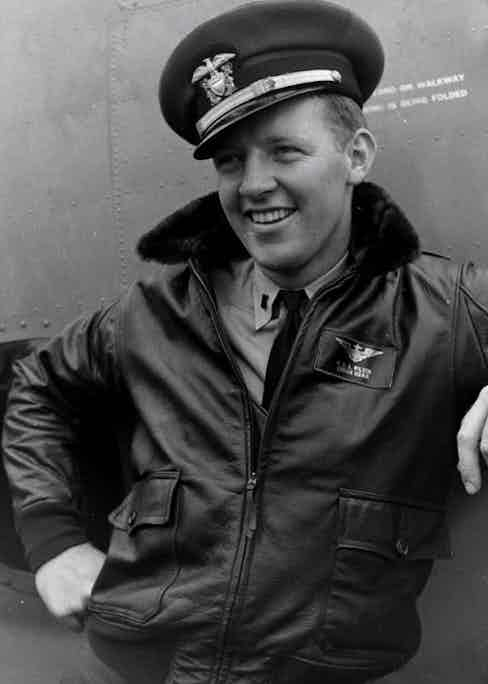 An American pilot poses by his plane wearing a traditional leather aviator jacket with a fur collar, circa 1942.