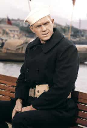 Steve McQueen wears a traditional navy pea coat with a double-breasted fastening in The Sand Pebbles, 1966.