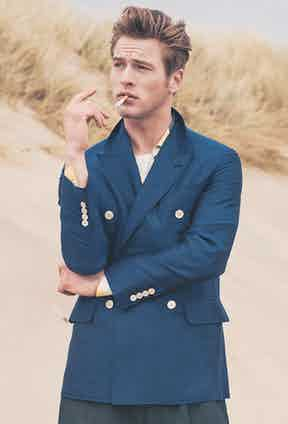 This blue silk double-breasted blazer by Caruso has naval-inspired qualities including the double-breasted fastening and brass buttons. Photograph by Simon Lipman and styled by Jo Grzeszczuk for Issue 45 of The Rake.