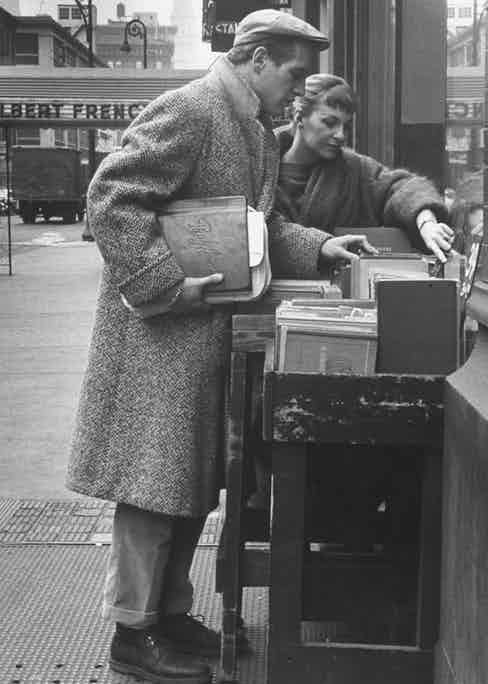 Paul Newman browses a bookstore with Joanne Woodward, wearing turn-up trousers, worker boots and a full-length overcoat. Photo by Gordon Parks/Time Life Pictures/Getty Images.