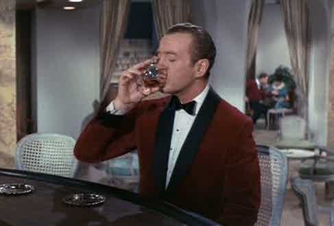 David Niven dons a red velvet dinner jacket with bow tie and white dress shirt as Sir Charles Lytton in The Pink Panther, 1963.