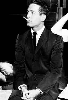 Paul Newman wears a single-breasted suit paired with a white shirt and solid coloured tie on the set of Rally Round The Flag, Boys!, 1958.