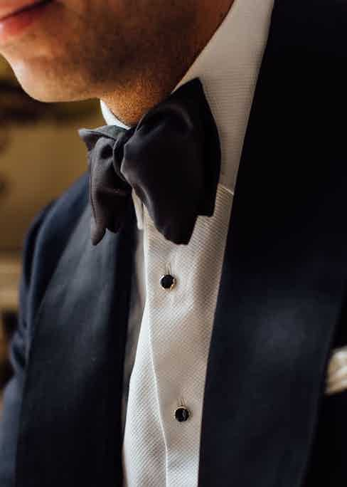 An ivory spun silk scarf, silver and onyx dress studs and links, and a moiré bow tie are all from Budd Shirtmakers and demonstrate the correct way to wear black tie. Photograph by Jamie Ferguson.