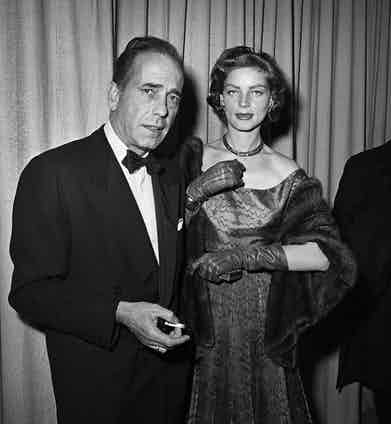 Humphrey Bogart looks effortlessly cool wearing black tie at the Academy Awards ceremony with his wife Lauren Bacall in Los Angeles, 1952. Photograph by Frank Worth, Courtesy of Capital Art/Getty Images.
