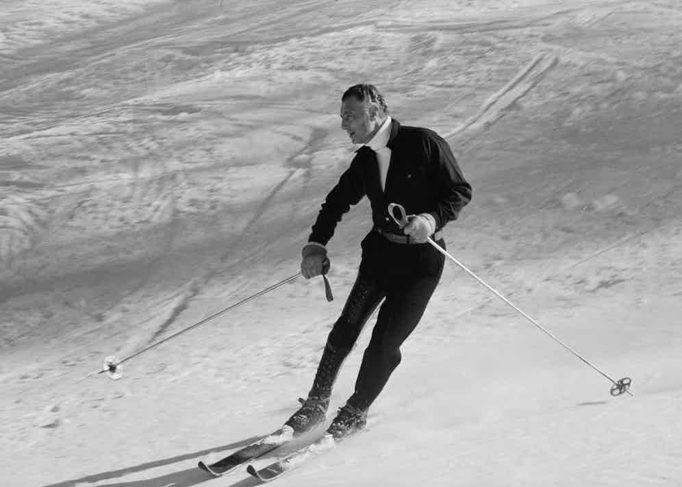 Gianni Agnelli looks sleek and sophisticated in an all-in-one dark ensemble with a belted waist paired with a white turtle neck while skiing near the Sestriere ski resort in Italy, 1967.