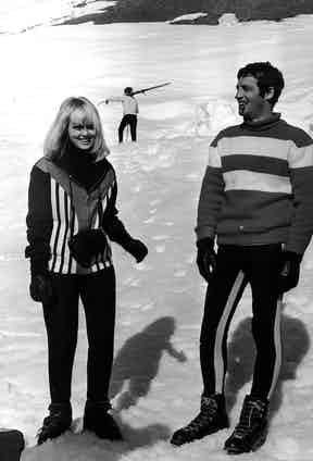 Jean-Paul Belmondo is the epitome of cool casual in a striped knitted jumper, ski leggings and lace-up snow boots with actress Mylene Demongeot in Megeve, France, 1966.