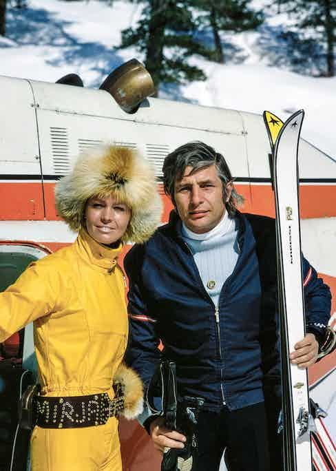 Gunter Sachs looks polished in a navy fitted ski jacket with a pale blue and white two-tone rollneck at the Swiss ski resort of St. Moritz with his wife Mirja Larsso, circa 1972.