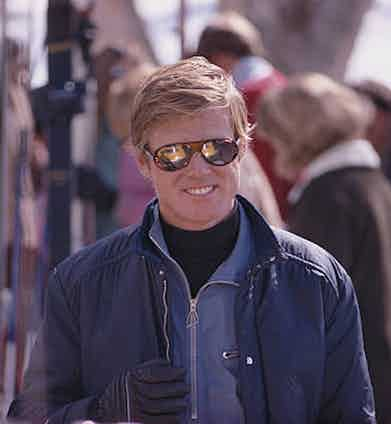 Robert Redford accessorises his simple yet sophisticated look with a pair of aviator sunglasses, a necessity on the sunny mountains. He is pictured here during the filming of Downhill Racer, 1969.