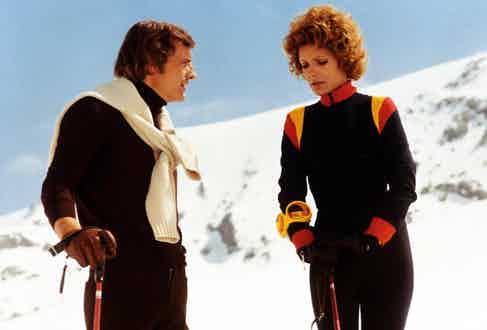 Former French ski champion Jean-Claude Killy layers his knitwear with a white jumper perfectly folded over his shoulders. He is pictured here with fellow actress Daniele Gaubert on the set Snow Job, 1972. Photo by Jacques Dejean/Sygma via Getty Images.