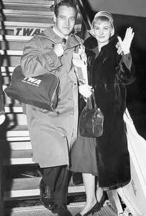 Paul Newman shows travelling can still be done with sophistication, wearing an overcoat, suit and black lace up Oxford shoes on his way to London with his new bride Joanne Woodward, 1958.