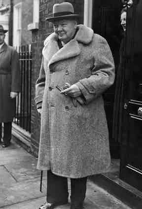 Winston Churchill wears a double-breasted teddy bear coat, a bowler hat and can be seen holding leather gloves to combat the bitter temperatures in London, 1940.