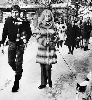 Gunter Sachs opts for a more casual and practical attire wearing a V-neck knitted jumper, shirt, snow boots and a large scarf while on holiday in La Madrague with Brigitte Bardot, 1967.