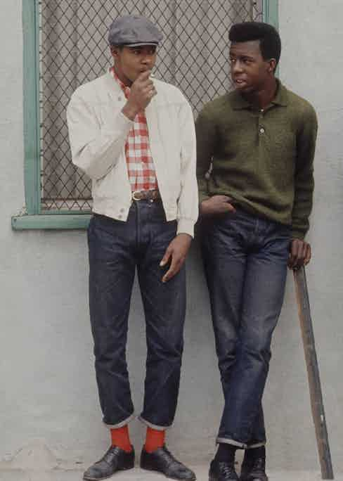 Preppy rebels from Los Angeles' Watts community purposefully dressed well to diffuse racial stereotyping in the 1960s. Here, one wears a peaked cap with a casual, considered look that includes an off-white blouson and turn-up jeans.