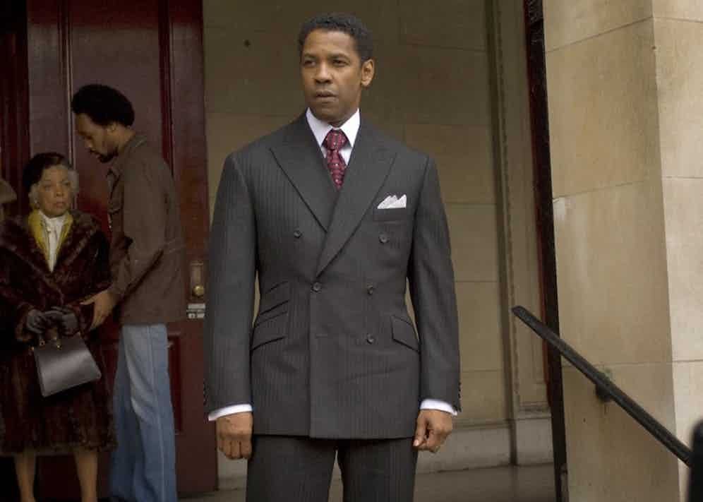 This is Lucas' most formal business look in the film which he wears before being arrested. The dark grey double-breasted pinstripe suit features a 6x2 button stance (the lower button left undone) and angular flap pockets, worn with a three-pointed silk pocket square, a burgundy and navy striped tie with yellow polkadots and a crisp white pointed collar shirt. The look is more Wall Street banker than heroin trafficking kingpin, but it works.