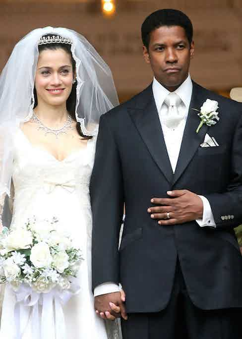 Frank Lucas' wedding attire features a white-on-white shirt and tie combination beneath a black peaked lapel, single-breasted suit with satin facings, topped off with a white boutonnière in his left lapel and a white silk handkerchief trimmed with black in his breast pocket.