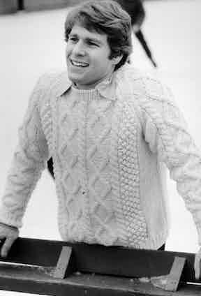 Ryan O'Neal pulls off the preppy, Ivy League look in an authentic Aran sweater with multiple motifs over a collared shirt in Love Story, 1970.