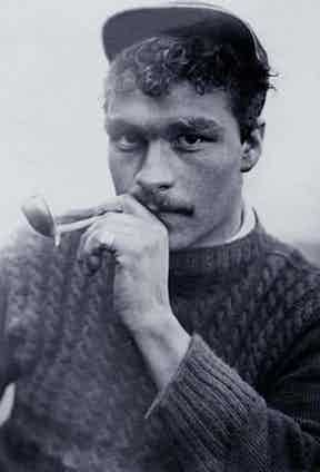 A fisherman from the Shetland Islands off the coast of Scotland smokes a pipe in his hand-knitted Gansey Sweater, circa 1920.