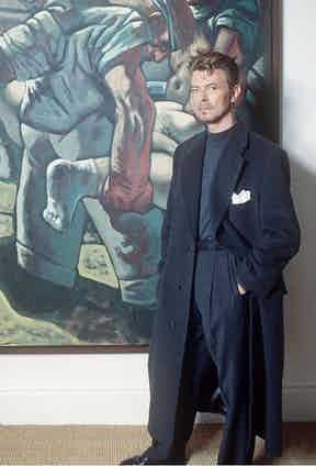 David Bowie was often photographed in trousers featuring deep pleats and wide legs. Here, he wears a tonal blue ensemble at the British Museum, 1994.