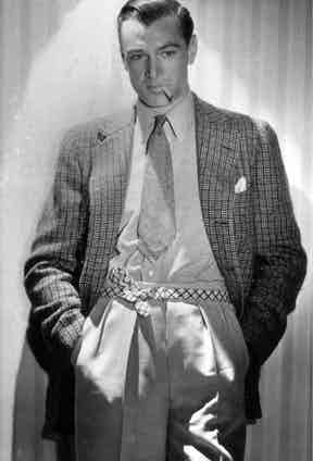 A slicked back Gary Cooper sporting an interesting checked belt to support his high-waisted, forward facing pleated trousers, circa 1937.