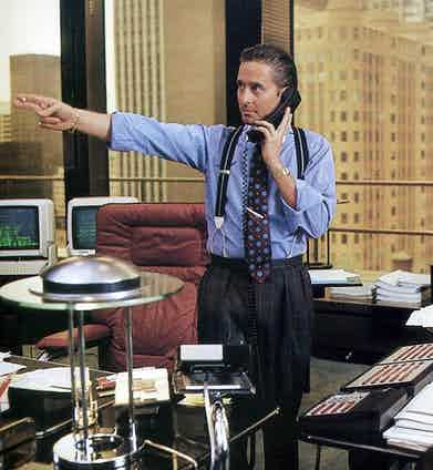 Michael Douglas as Gordon Gekko in the 1987 classic Wall Street. He wears windowpane pleated trousers, supported with two-tone braces for a formal business look.
