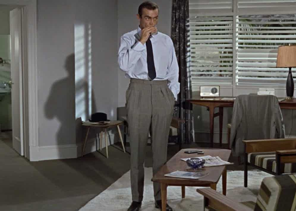 The inimitable Sean Connery as James Bond in Goldfinger, 1964. Connery went to tailor Anthony Sinclair for his drape cut suits, and no doubt his traditional pleated trousers. Here, he wears a style known as English pleats, in sharkskin grey flannel.