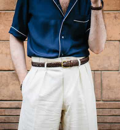 Further underlining the informality of Hollywood tops, Aleks Cvetkovic wears his cream Edward Sexton trousers with a woven leather belt and a piped pyjama shirt from Marol, available from The Rake Atelier.
