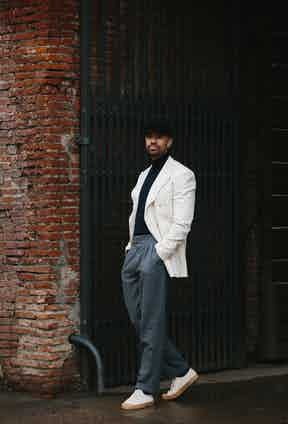Jonathan Edwards in bespoke separates by Polish tailor Maciej Zaremba replete with reverse pleats in a light grey flannel. He dresses his down with a casual pair of canvas sneakers. Photo by Jamie Ferguson.