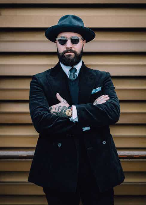 Jared Acquaro demonstrating the art of tonal simplicity with a peaked lapel, double-breasted black corduroy suit and matching trilby hat.