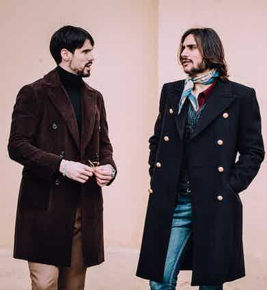 Sergio Guardi of Barbenera in a naval bridge coat, talks with a friend in a sumptuous corduroy double-breasted overcoat.