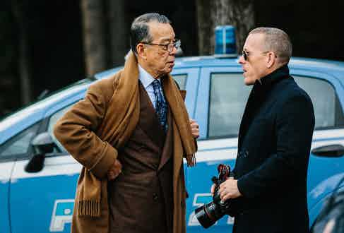 Yukio Akamine wears a double-breasted chocolate flannel suit with a light blue poplin shirt as he speaks with the master of street-style photography, Schott Schuman.