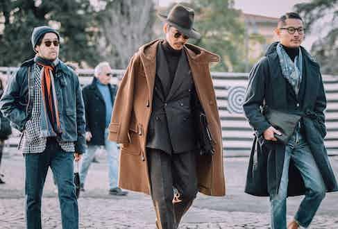 BEAMS Fashion Director Shuhei Nishiguchi showcasing how brown tonal tailoring is done with a duffle coat hanging across his shoulders.