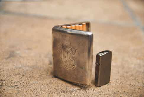 William's choice of smokes for the evening is a pack of Tor Oriental, which is a marinated Turkish tobacco. During the day, however, it's a pack of Marlboro Red, which he keeps in a silver cigarette case from 1915 engraved with his initials.