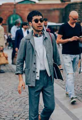 High-waisted tailored trousers draw the eye upwards towards a chore jacket in a lightweight striped cloth, layered over a white jacket, white T-shirt and neckerchief.