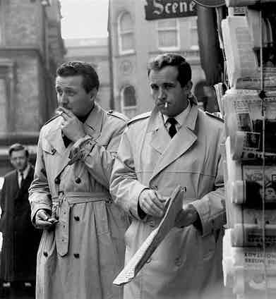 Patrick Macnee and Ian Hendry sport varying trench coats for the filming of TV series The Avengers in London, 1961. The left has quilted leather buttons and a gun flap, whereas the right has tortoiseshell buttons and a cleaner silhouette.
