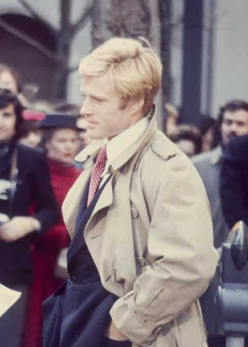 Robert Redford dons a classic taupe trench coat paired with a dark suit and white shirt with a pointed collar. Pictured here in The Way We Were, 1973.