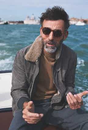 Light grey suede and beige shearling jacket, Brunello Cucinelli; camel wool jumper, Moncler; slate grey wool trousers, AMI; amber tortoise and tobacco lenses sunglasses, The Bespoke Dudes at The Rake. Sea green leather belt, property of The Rake.