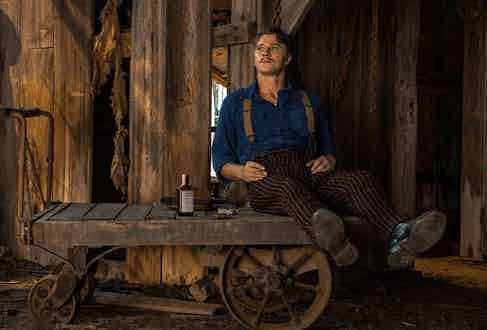 Set in the 1940s, Mudbound's Jamie McAllan returns from war to work on his brother's farm. Even so, he wears pinstriped tailored trousers and braces over a heavy cotton blue shirt.