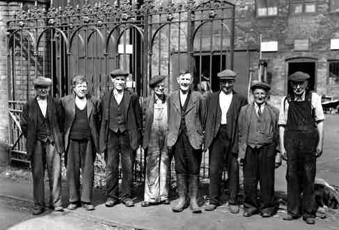 Loose-fitting overalls and generously cut tailoring allow for movement and flexibility for factory workers at Ironbridge, England circa 1940s.