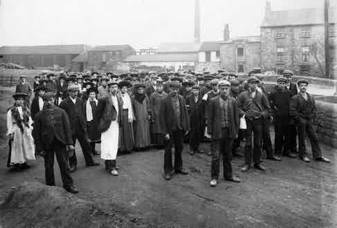 Factory workers sport high-buttoning jackets, mostly single-breasted, and peaked caps in Doncaster, England, circa 1880s.