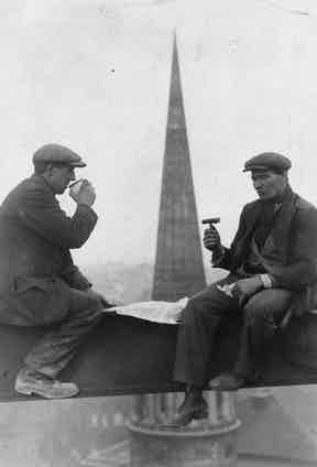 Two roofers take a break for lunch in front of the spire of All Souls Church, London, circa 1940. Their tailored jackets have patch pockets, peaked lapels and enough movement to allow them to work without constraints.