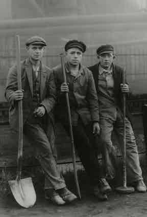 Workers from the late 19th century wear tailored jackets, waistcoats, peaked caps and heavy-duty boots, a look that is often imitated today.