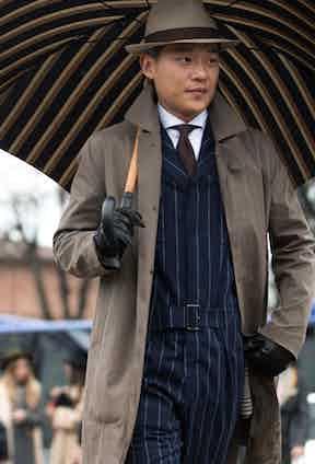 Seongsu Kim wears a tailored, belted, fly-front siren suit in a navy pinstripe beneath a neutral macintosh coat.