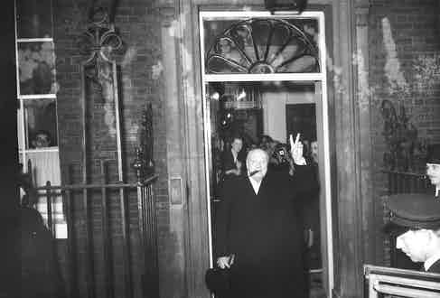 With his fingers raised in the familiar V sign, Churchill leaves No.10 Downing Street for the last time, 1955.