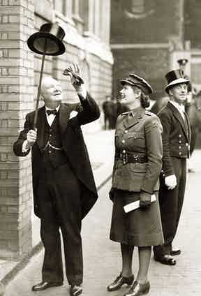 Churchill in tails, sporting his signature spotted bow tie, a silk top hat and cane with his daughter Mary, 1943.