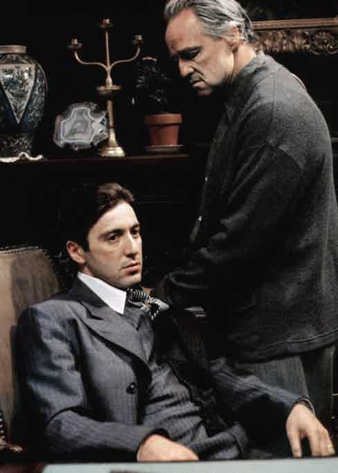 The grey striped three-piece suit and black and silver striped tie signifies a shift in Corleone's power. Marlon Brando's character Don Vito Corleone is dressed far more casually in grey slacks and woollen cardigan.