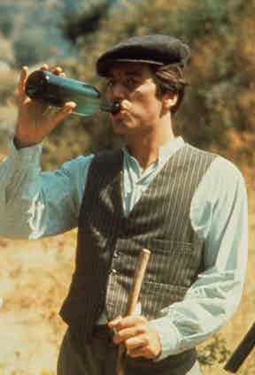 During the scenes in Sicily, the exiled Michael Corleone's workwear consists of a grey pinstriped waistcoat and trousers over a pale blue Mandarin-collar shirt and a grey peaked cap.